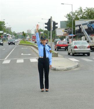 Polici zyrtar i uniformuar gjatë rregullimit të komunikacionit në udhëkryq (si në fotografinë):