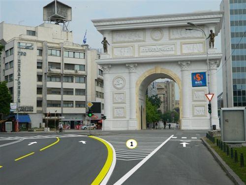 Në fotografi është paraqitur një pjesë e rrugës automobilistike me: