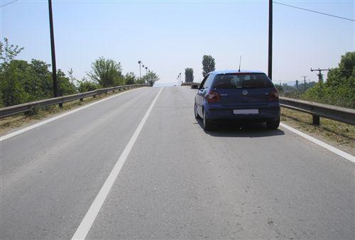 Në një pjesë të rrugës publike, urë apo mbikalim të treguar në fotografi, shoferi i veturës: