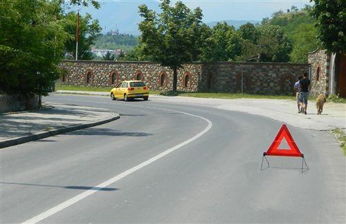 Shenja e posaçme me të cilën shënohet automjeti i ndalur në vend jo mirë të dukshëm, jashtë vendbanimit (si në fotografi) vendoset në rrugë, pas automjetit të ndalur: