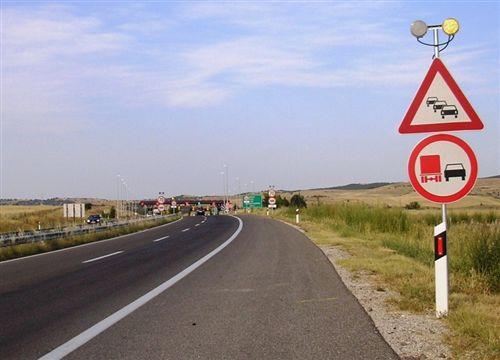 Sipas shnejave të komunikacionit të vendosura (si në fotografi) shoferi i automjetit has në një pjesë të autostradës, në të cilën: