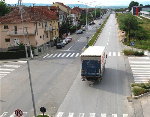 Shoferi i automjetit transportues të mallrave, ku masa më e madhe e lejuar e së cilës është më e madhe se 3.500 kg, kur qarkullon në rrugë publike në vendbanim (si në fotografinë), në të cilën ekzistojnë më së paku dy korsi komunikacioni për lëvizje në të njëjtën kahe: